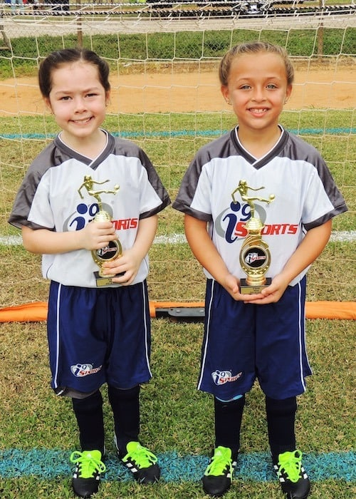 twin girls with soccer trophies after-school activities