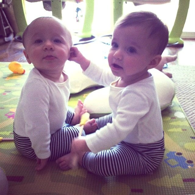 twin babies sitting on the floor out the door with twins