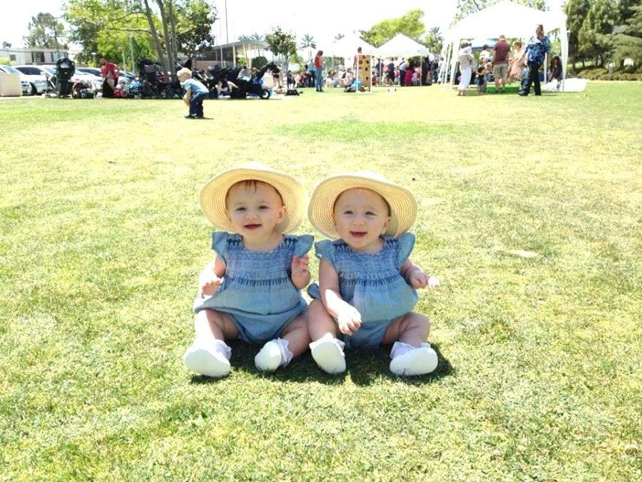twin girl babies sitting on the grass out the door with twins