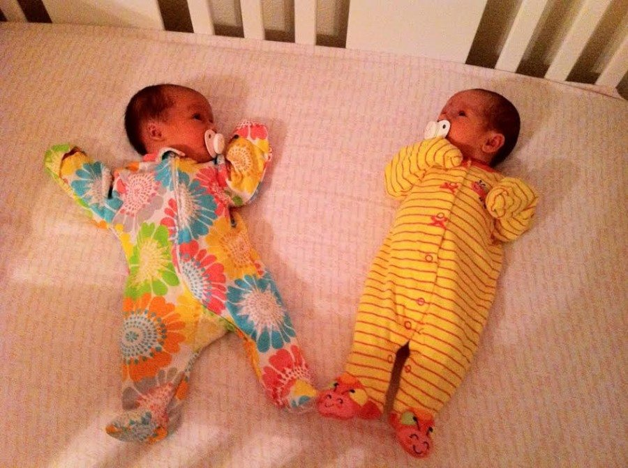 twin infants in a crib off pacifiers