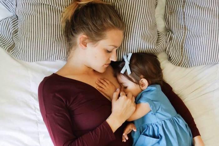 mom breastfeeding a baby lying on a bed feeding twins