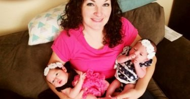 Mother with two baby twins in her arms