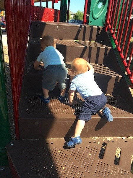 twins climbing up playground gym need to crawl