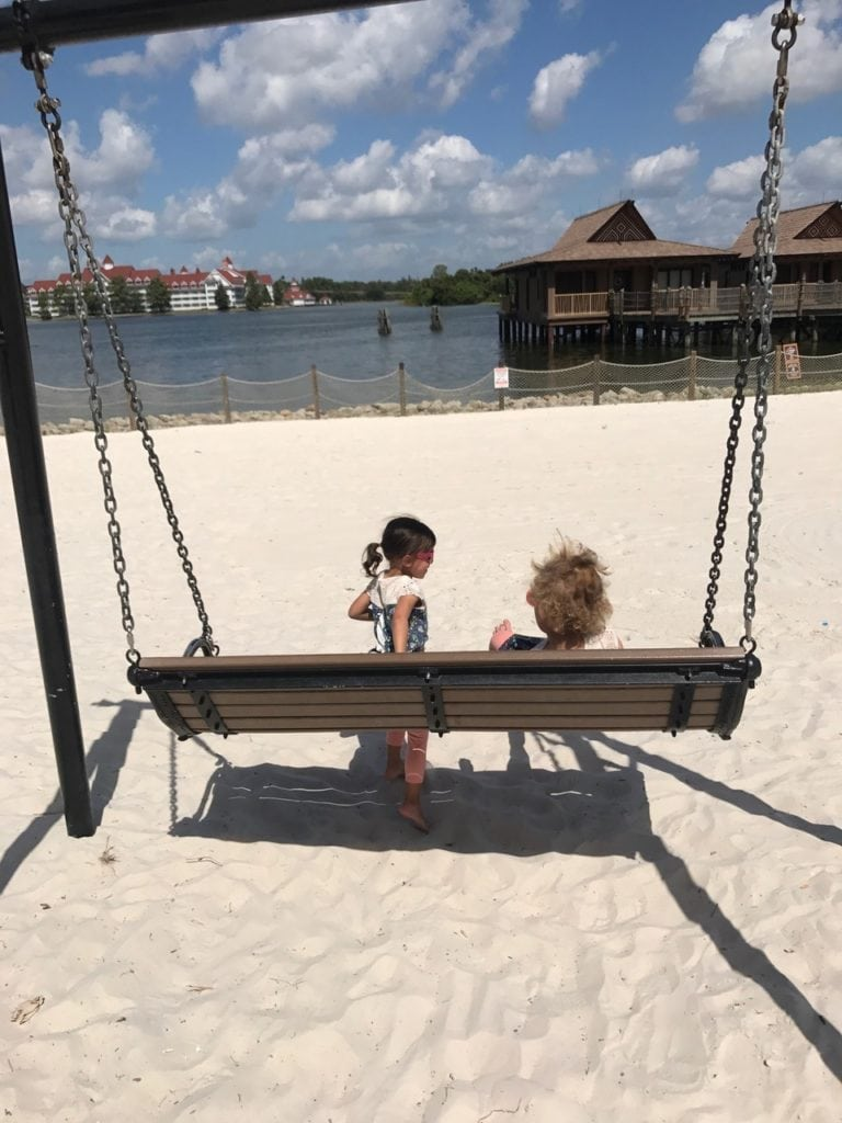 girls sitting on swing bench on the beach disney world with twins