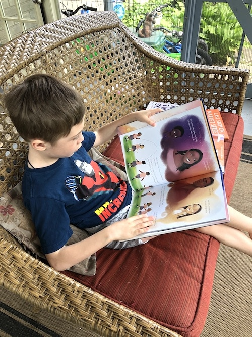 boy reading books to diversify