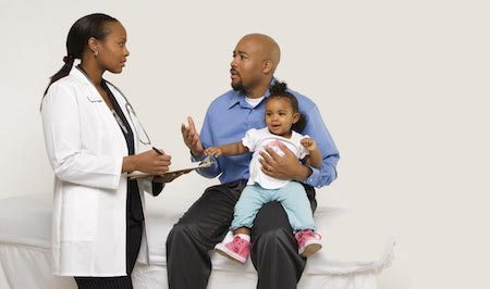 doctor talking to dad holding child doctor visits