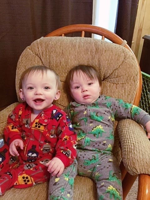 twin boys 1 year olds sitting in a chair together ear tubes