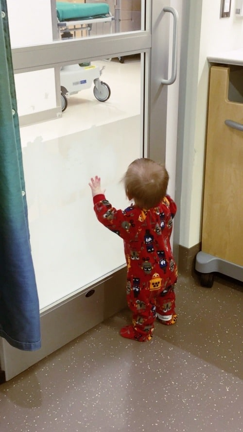 1 year old boy standing at glass door in hospital ear tubes