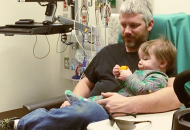dad holding 1 year old boy waiting to get ear tubes surgery