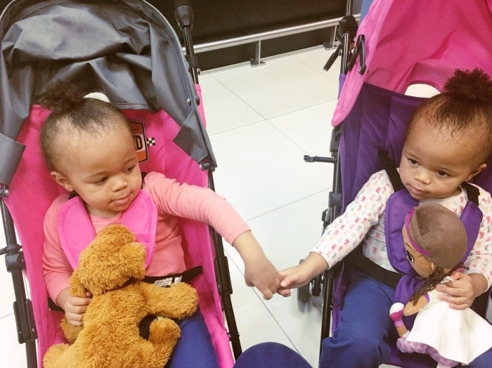twins in strollers holding hands family vacation
