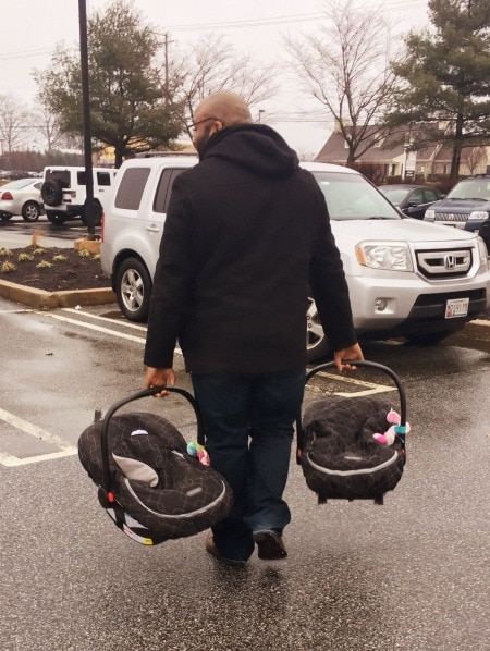 dad carrying car seats family vacation