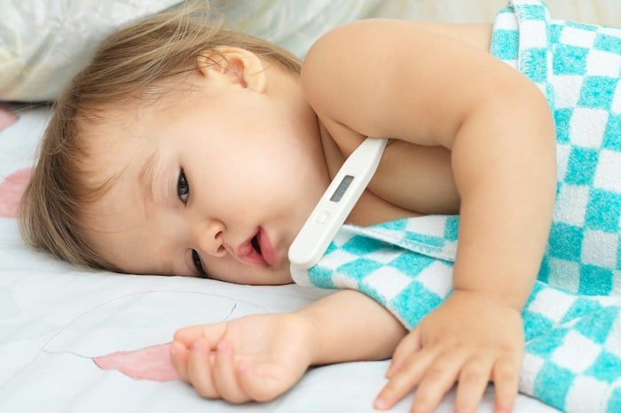 toddler laying down sick with thermometer under her armpit the flu