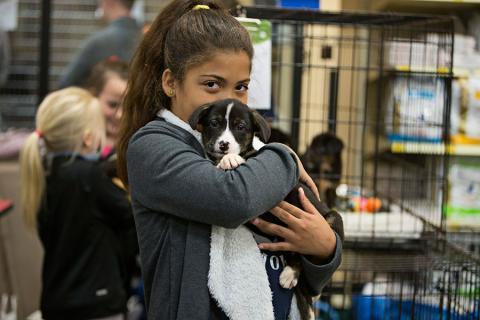 girl holding puppy kids reach their goals
