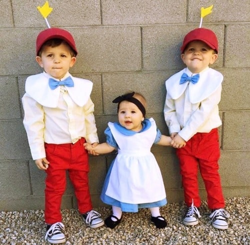 twin boys dressed up as tweedle dee and tweedle dum and their baby sister in the middle dressed up as Alice in Wonderland