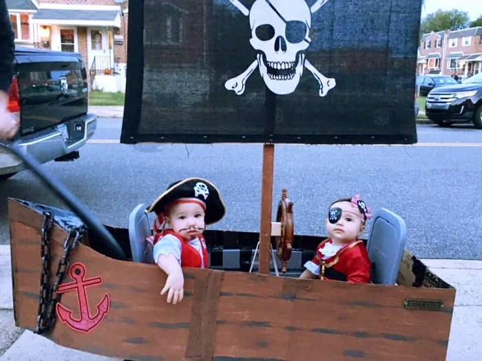 twin babies dressed as pirates sitting in a wagon dressed up as a pirate ship