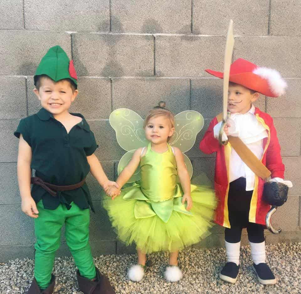 twin boys dressed as peter pan and captain hook with their younger sister dressed as tinkerbell in the middle