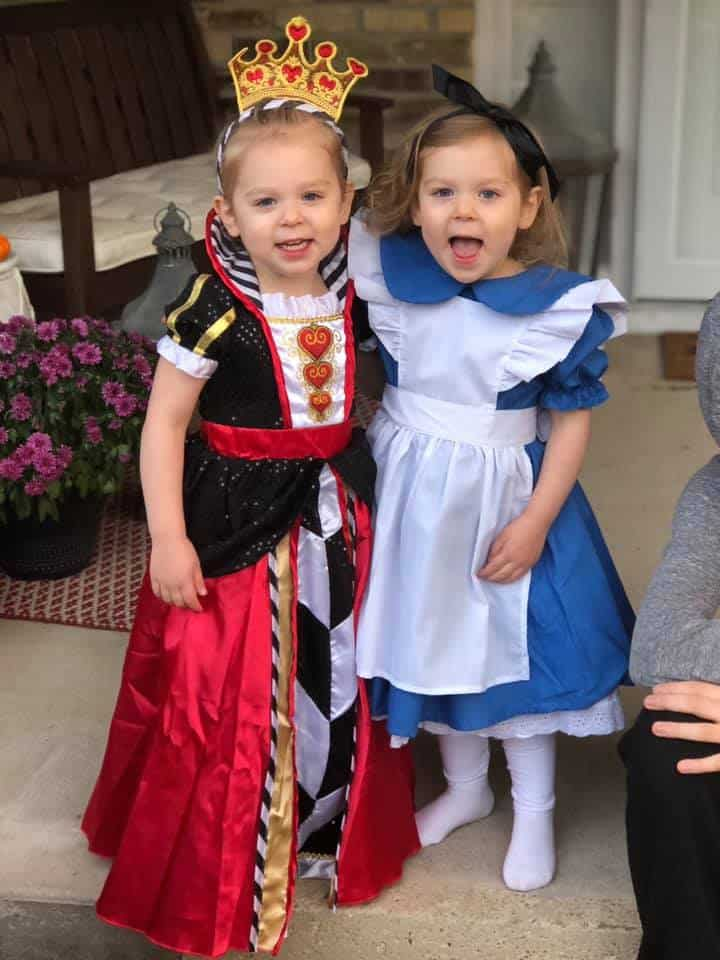 twin girls dressed up as alice and queen of hearts from alice in wonderland