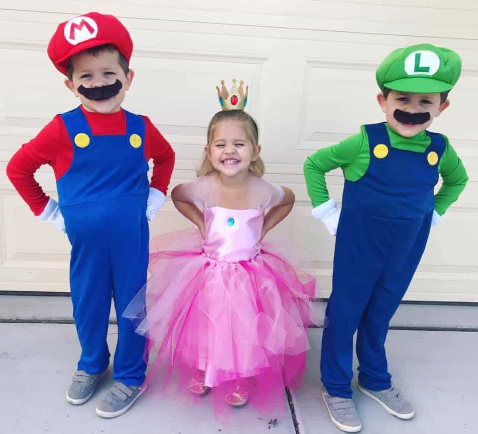 twin brothers dressed as mario and luigi and their sister in the middle dressed up as princess peach