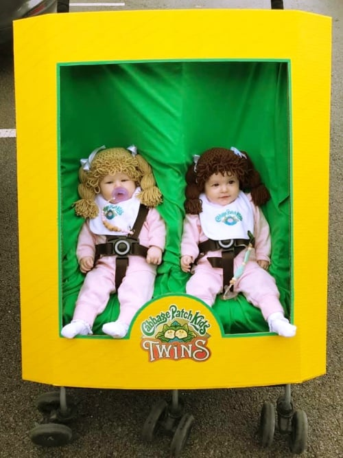 twin baby girls dressed up as cabbage patch kids and sitting in a stroller that's made up to look like a box