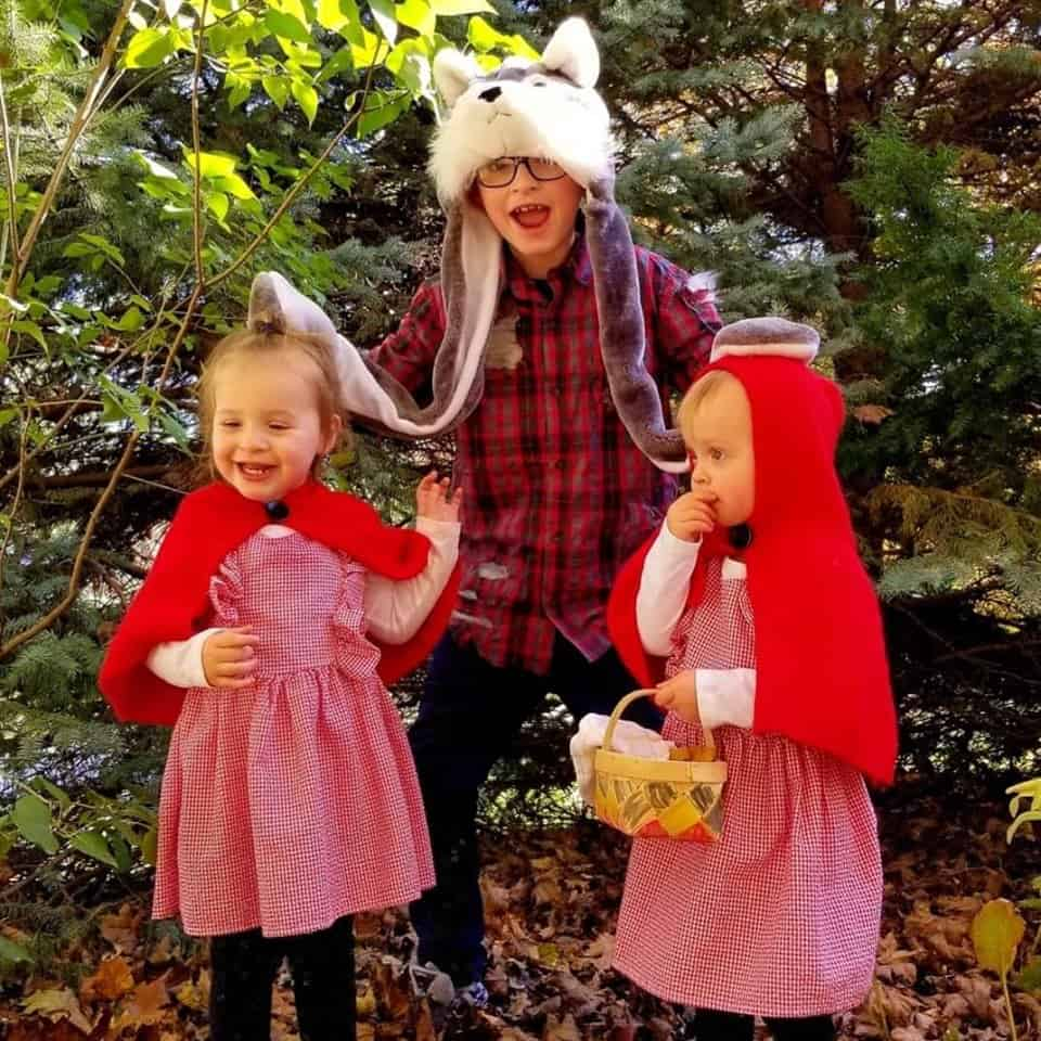 twin toddler girls dressed up as little red riding hood and their older brother dressed up as the wolf in the center