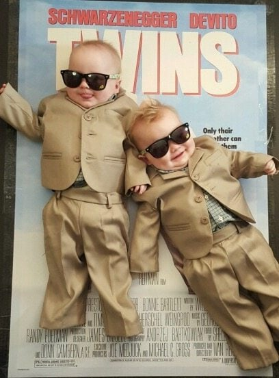 infant twin boys dressed up like the poster for the movie Twins