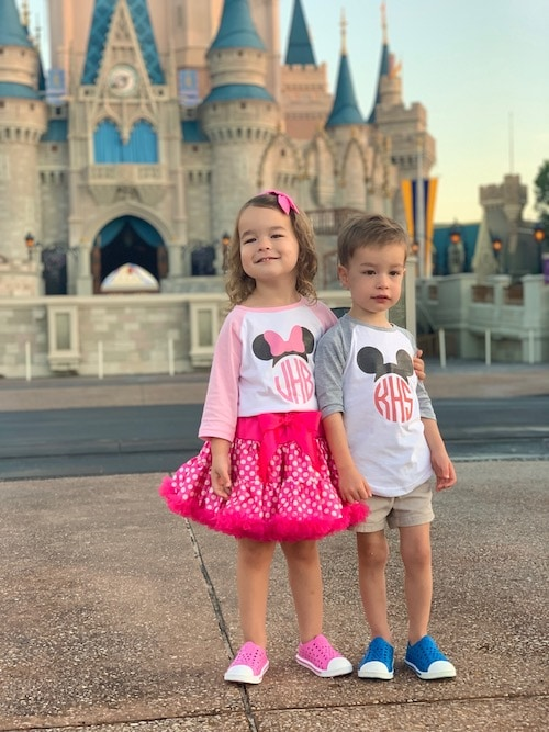 twin 3 year olds in front of cinderella's castle disney world alone