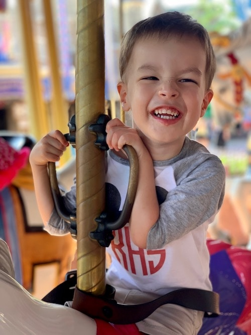 boy riding carousel disney world alone