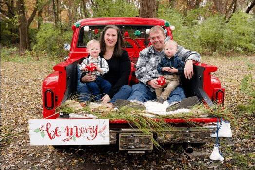 family with identical twin boys 1 year old sitting in a truck decorated for the holiday moments