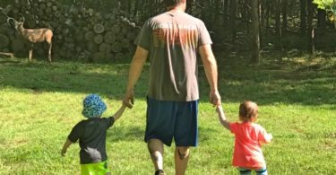dad walking in grass with toddler twins welcome spring
