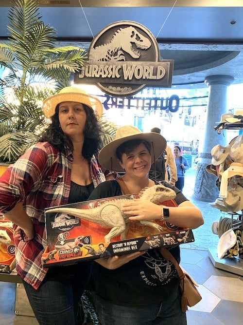 two women wearing jungle hats and holding a toy dinosaur in a gift shop at Jurassic World - The Ride