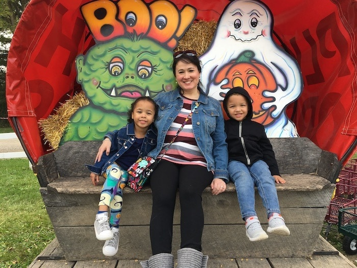 Mother with Twin girls on bench, smiling