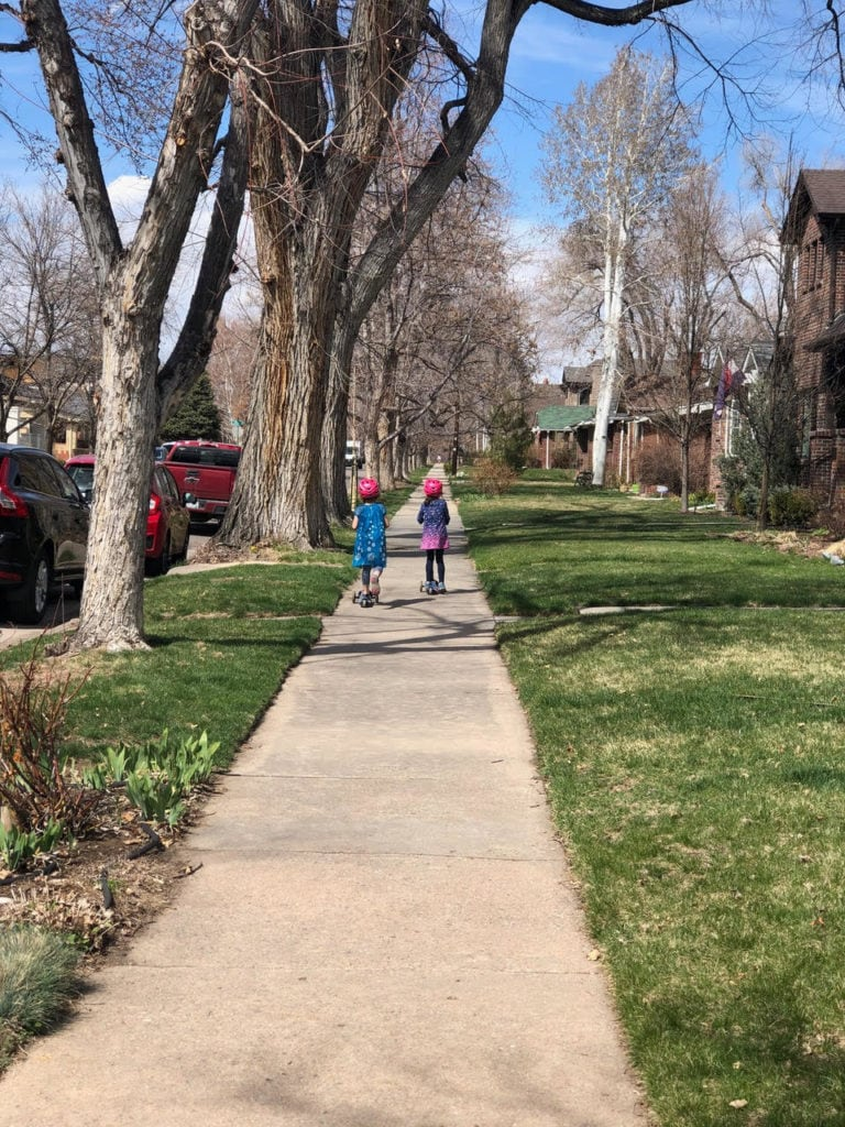 two girls walking down a sidewalk not traveling
