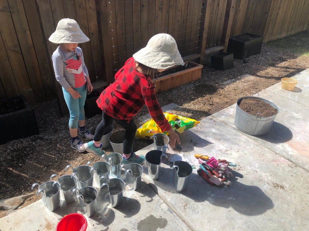 two girls playing with buckets and dirt not traveling