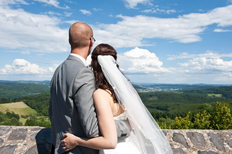 Bride and Groom looking at forest landscape