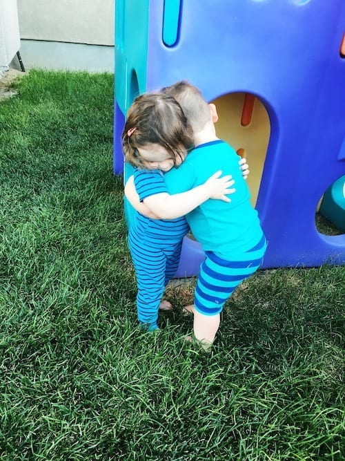 twin toddlers hugging in the back yard look forward