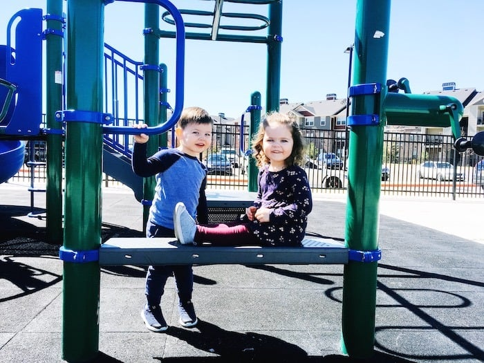 twin toddlers on playground equipment look forward