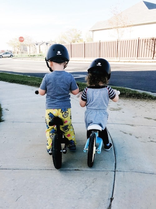 twin toddlers riding balance bikes with helmets look forward