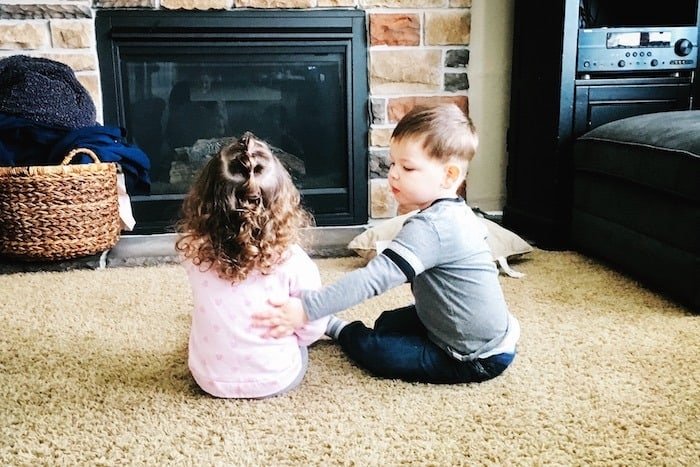 twin toddlers sitting on carpet look forward