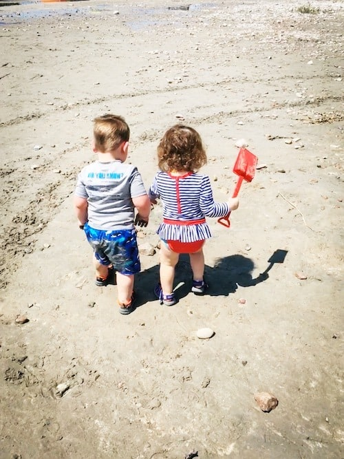 twin toddlers on the beach sand look forward