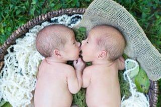 newborn twins snuggling in a basket