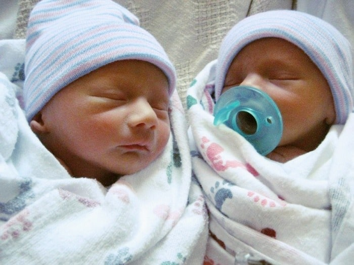 newborn twins sleeping and wrapped in blankets