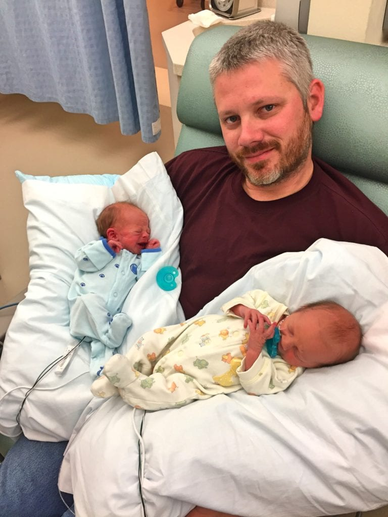 dad holding twins time in the nicu