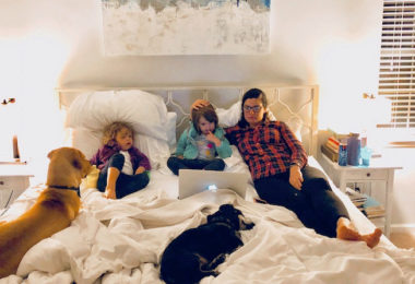 twin girls and mom in bed with 2 dogs