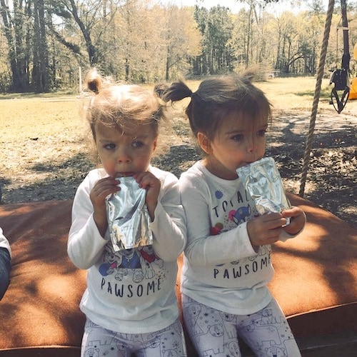 twin girls drinking juice boxes at the park parenting
