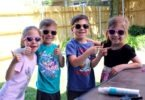 four kids wearing sunglasses summer shopping