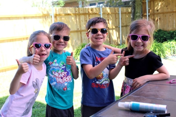 four kids wearing sunglasses summer shopping