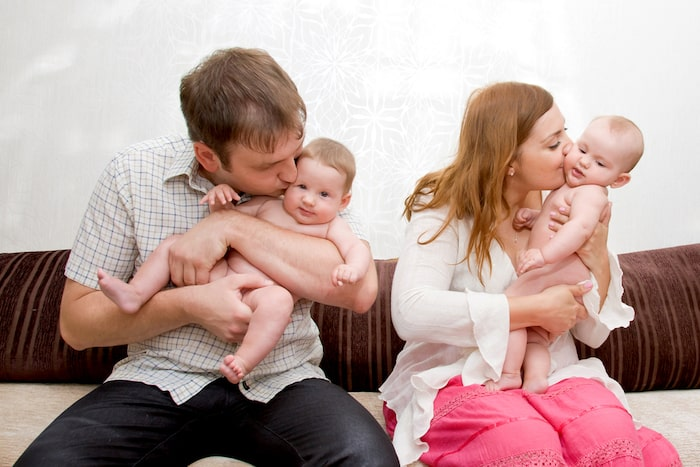 mom and dad kissing baby twins gift giving