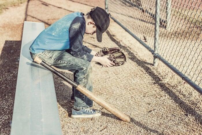 junior high school boy with baseball bat sitting on bench