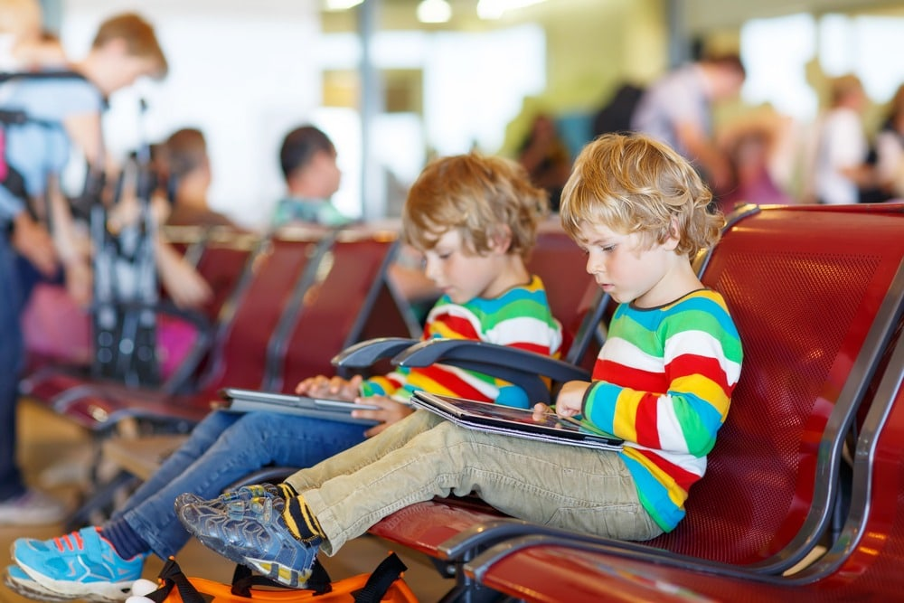 twins sitting at airport twin travel