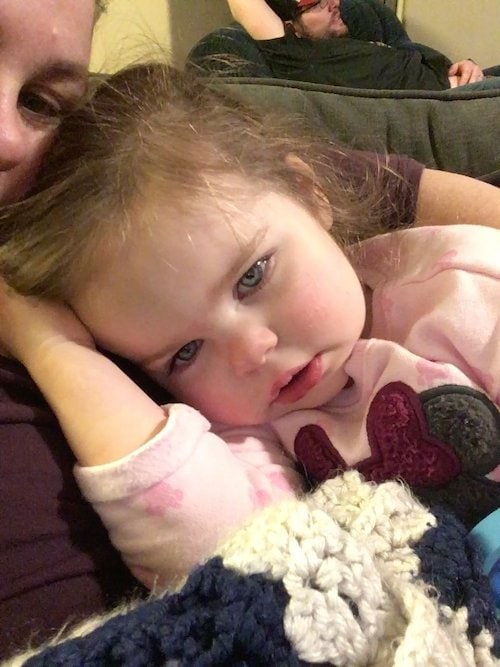 little girl snuggled up with mom cold and flu season